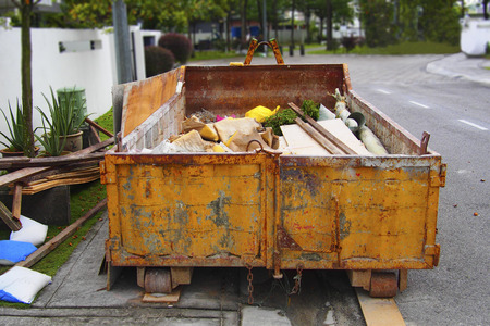 Yellow construction rubbish bin with loads, home renovation