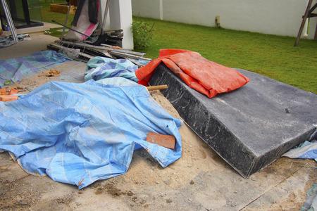 black plastic basin, bricks and plastic sheet  on the sand at construction site Standard-Bild