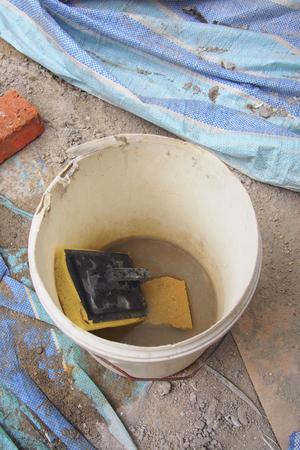 Cement sponge trowel inside a plastic bucket Standard-Bild