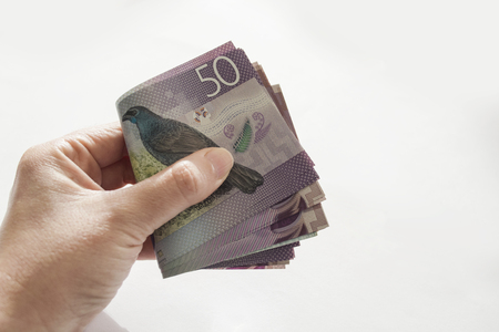 Woman holding a stack of New Zealand currency Standard-Bild
