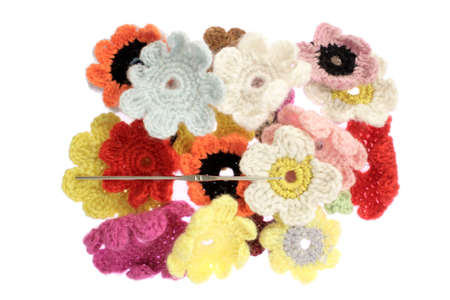 gifting: close up of woolen flowers against white blackguard.