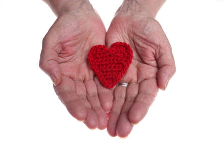 gratuity: Old womans hands giving woollen heart  Stock Photo