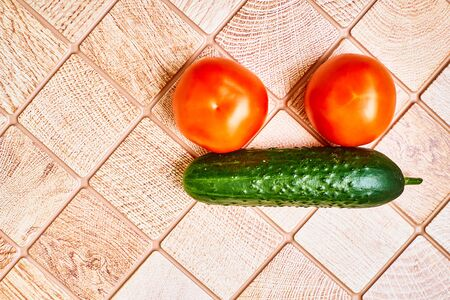 Two red tomatoes and green cucumber