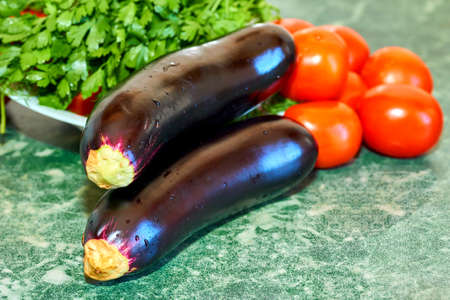 Cooking delicious and healthy food.Eggplants, tomatoes and parsley