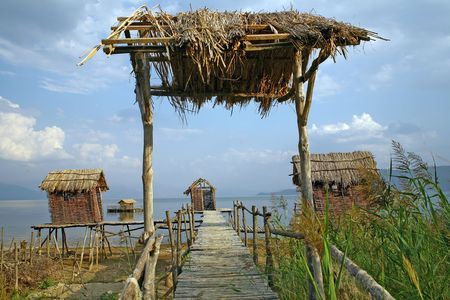 fishermens: Fishermen`s village with houses made of cane and wooden docks in southern Europe. Stock Photo