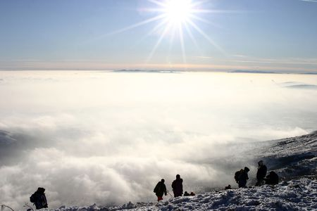 A group of mountin climbers above the clouds at mountain
