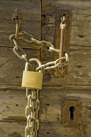 Old wooden door with padlock and chain photo