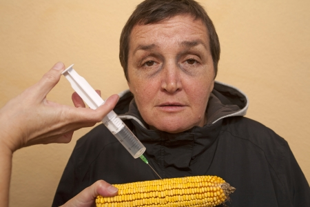 Genetically modified organism, ill woman with GMO corn cob