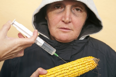 genetically modified organism: Genetically modified organism, ill woman with GMO corn Stock Photo