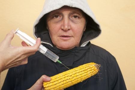 Genetically modified organism, ill woman with GMO corn Stock Photo