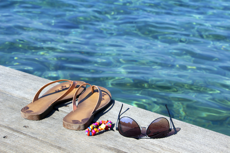 flipflop: Flip-flop, sunglasses and  bracelets on wooden dock near the sea Stock Photo