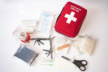 safety first: Open first aid kit with bandages, scissors, \triangle scarf\, syringe, plaster, knife, tools, gauze, etc Stock Photo