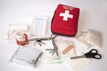 "Open first aid kit with bandages, scissors, ""triangle scarf\"", syringe, plaster, knife, tools, gauze, etc"