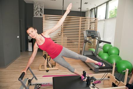 reformer: Exercise on pilates device reformer at gym