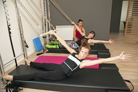 Exercise on pilates wall unit with instructor at gym Stock Photo