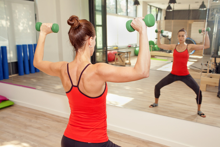 trainer device: Girl is exercising pilates using weights in front of the mirror Stock Photo