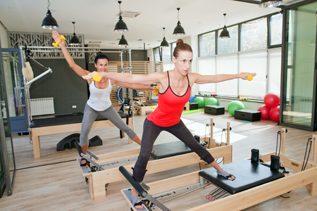 Girls are exercising pilates with pilates weights