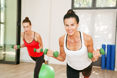 pilates studio: Girls are exercising pilates with pilates balls and weights