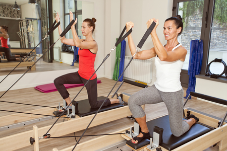 pilate: Two girls are exercising pilates using pilates device reformer