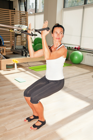 trainer device: Girl is exercising pilates using pilates wall unit