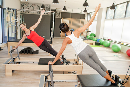 indoors: Two girls are exercising pilates using pilates device reformer
