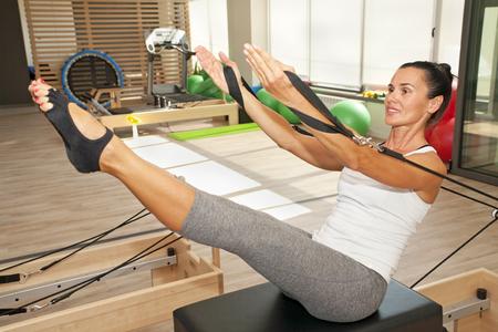 ejercicio: La muchacha est� haciendo ejercicio de pilates reformador mediante dispositivo pilates Foto de archivo