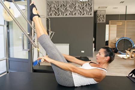 pilates: Girl is exercising pilates using pilates device   Stock Photo