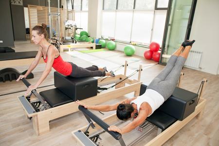 reformer: Two girls are exercising pilates using pilates device reformer