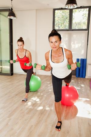 Girls are exercising pilates with pilates balls and weights