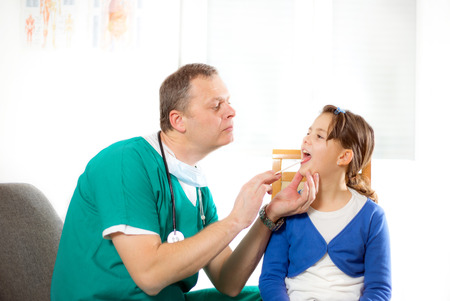 pharyngitis: Pediatrician checking little girl throat