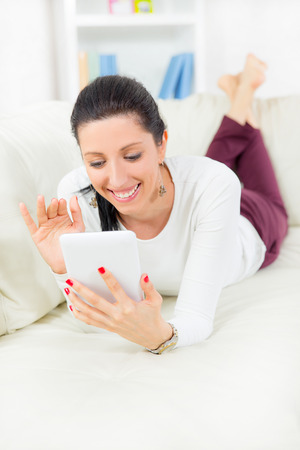 Smiling young woman with tablet pc laying on sofa photo