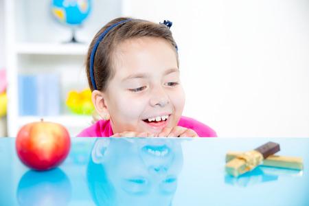 barrettes: bambina con la mela e cioccolato Archivio Fotografico
