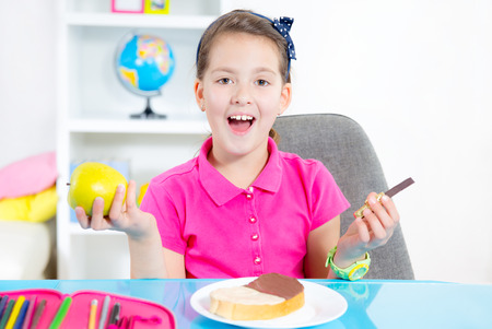 Happy smiling little girl looking a slice of bread with chocolate spread for snack photo