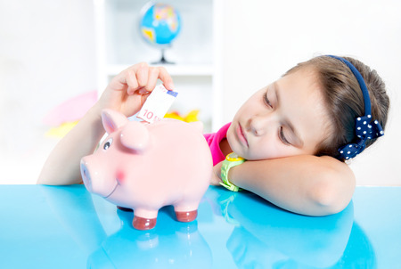 thrifty: child with piggy bank Stock Photo