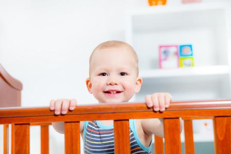 Baby boy standing in crib photo