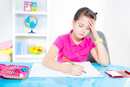 Smiling Caucasian girl doing homework at home  Zdjęcie Seryjne
