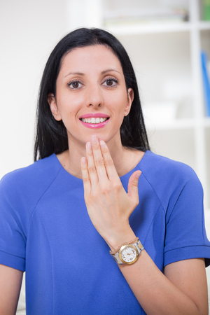 oreja: sonriente mujer sorda usando un lenguaje hermoso signo Foto de archivo