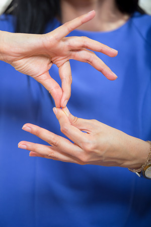 hand signs: Deaf woman using sign language, close up