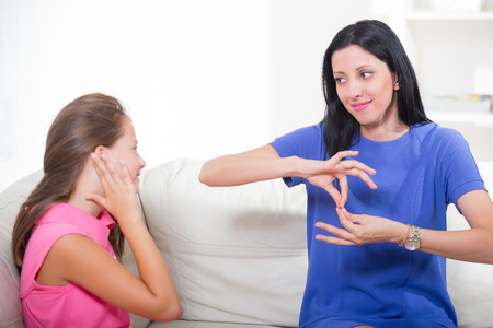 Smiling deaf girl learning sign language Stock Photo