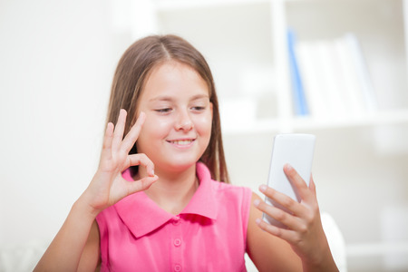 Smiling deaf girl talking using sign language on the smartphones cam
