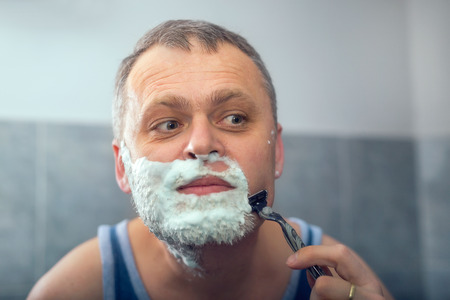 40 year old man: Mature handsome man shaving in front of mirror