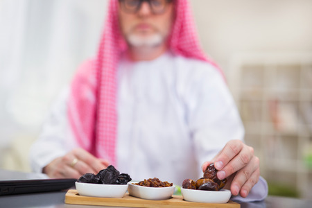 hombre arabe: Arabian man takes dried fruits. Focus on fruit