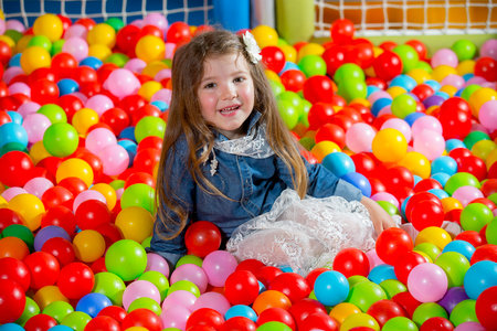 playcentre: A girl in the playing room with many little colored balls