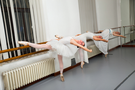 a rehearsal: Row of female ballet dancers practicing at barre in rehearsal room Stock Photo