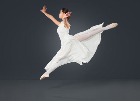 Beautiful female ballet dancer on a grey background. Ballerina is wearing a tutu and point shoes. Stock Photo