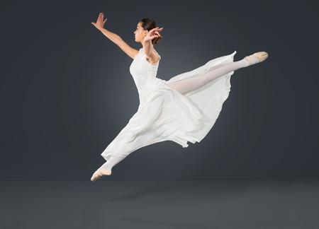 bailarina de ballet: Hermosa bailarina de ballet femenino sobre un fondo gris. La bailarina está vestido con un tutú y zapatos de punto.