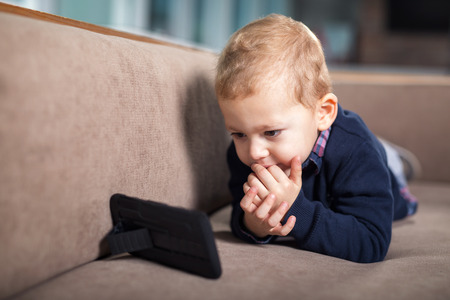 looking at baby: Little boy playing and touching a mobile phone