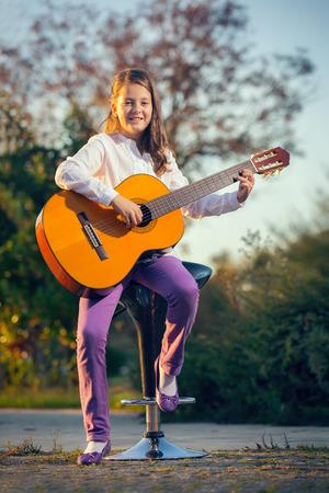 ni�as sonriendo: Ni�a que toca la guitarra ac�stica fuera