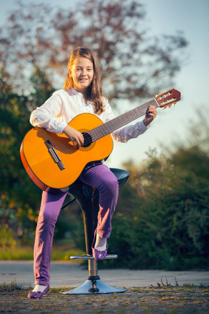beautiful nature: Little Girl Playing Acoustic Guitar Outside