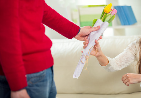 brings: Young guy brings flowers to his girlfriend. Selective focus Stock Photo